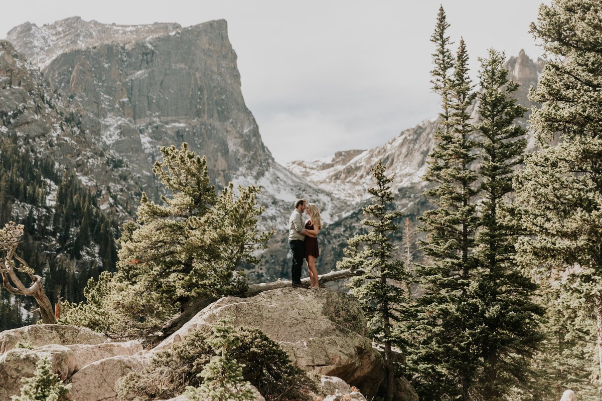 faraway_photo_of_engaged_couple_standing_on_rock_by_mountains_.jpg