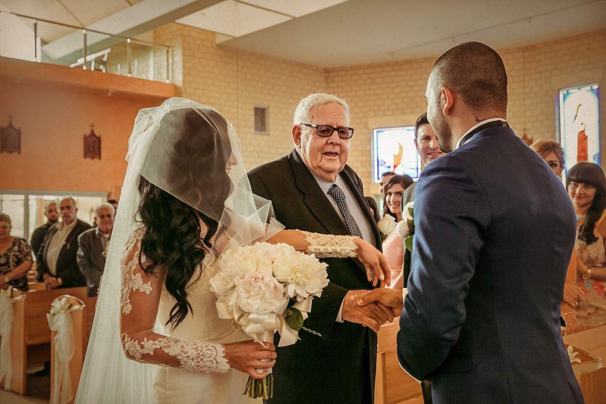 father_giving_away_bride_to_groom_in_church_wedding_ceremony.jpg