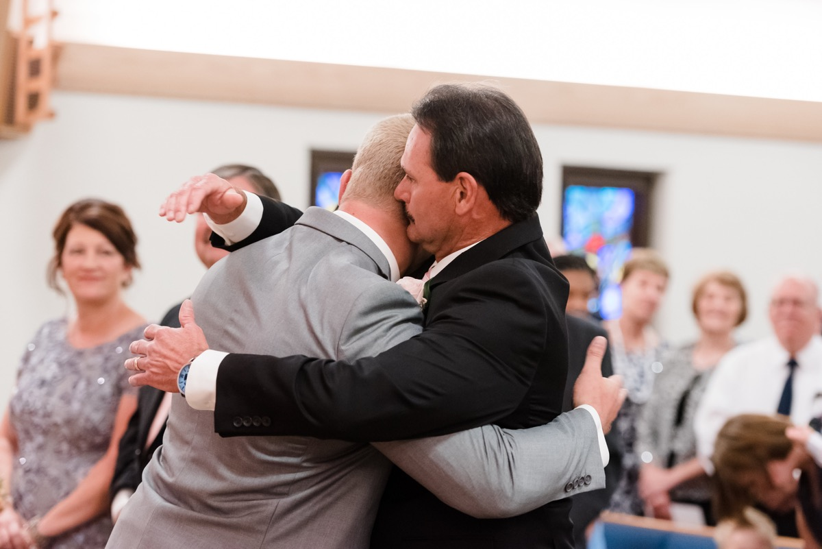father_hugging_groom_at_end_of_wedding_aisle.jpg