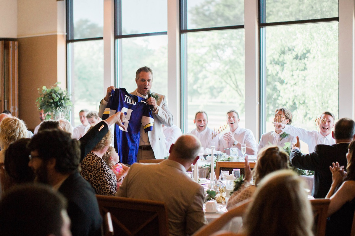 father_of_the_bride_making_speech_reception_holding_vikings_jersey.jpg