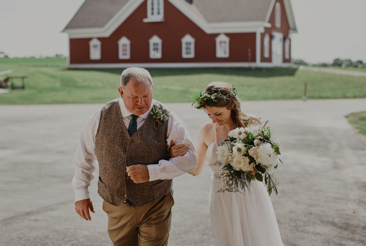 father_of_the_bride_walking_her_down_outdoor_farm_aisle.JPG