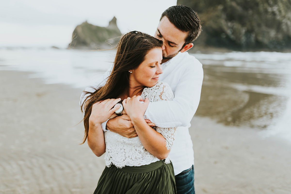fiance_holding_woman_in_arms_oregon_beach.jpg