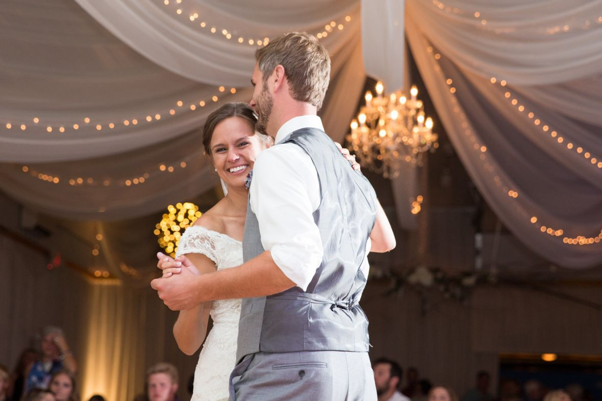 first_dance_husband_and_wife_chandelier_and_white_drapes.jpg