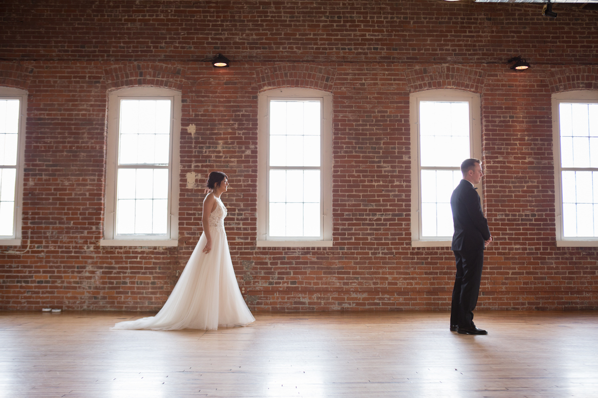 first_look_bride_walking_towards_groom_bright_brick_walls.jpg