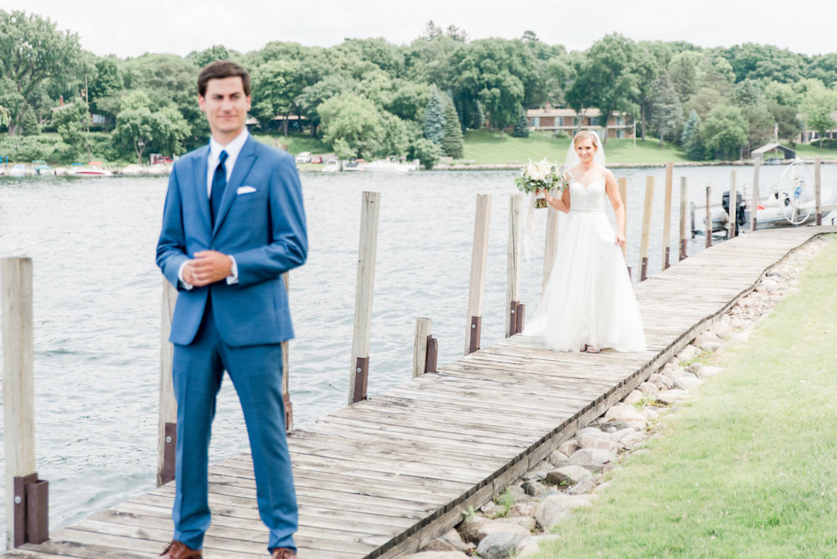 first_look_groom_in_navy_bride_walking_along_lake.jpg