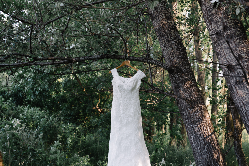 fitted_lace_bridal_gown_hanging_wooden_hanger_tree.jpg