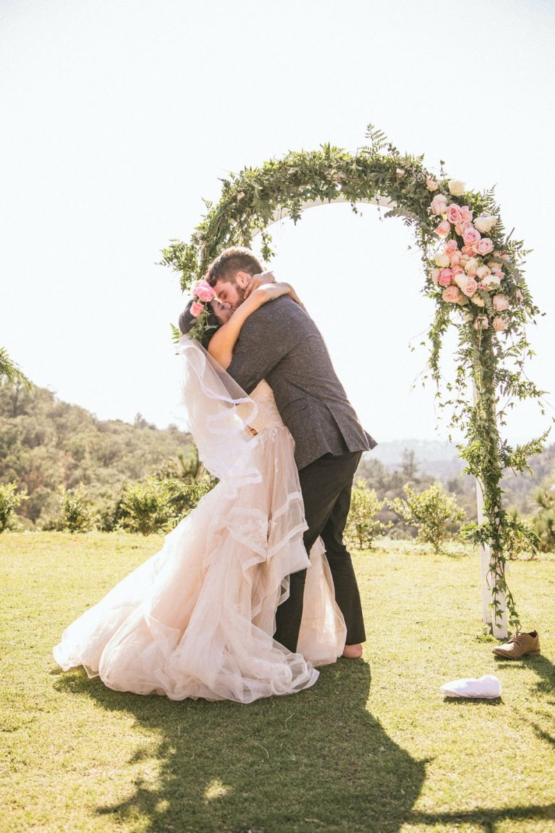 flower_crown_details_kissing_bride_and_groom.jpg