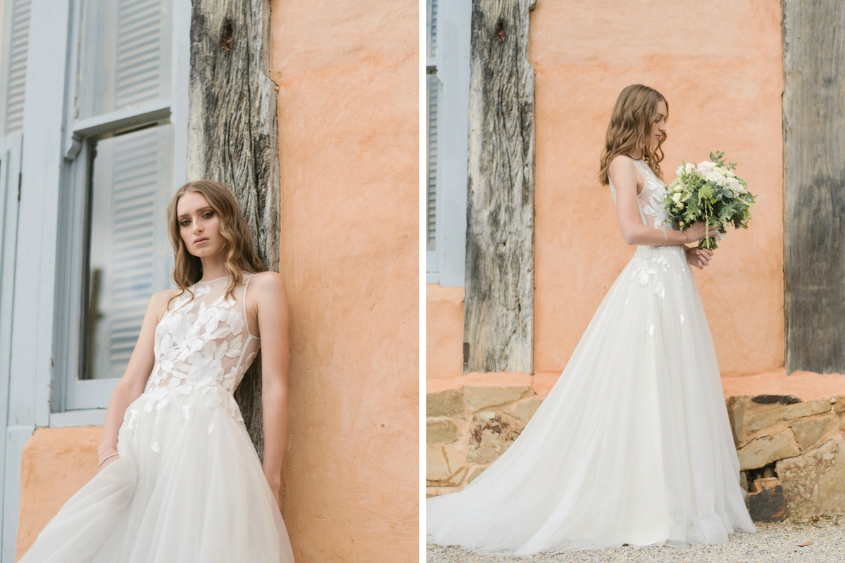french_bride_in_floral_wedding_gown_standing_againt_rustic_peach_building.jpg
