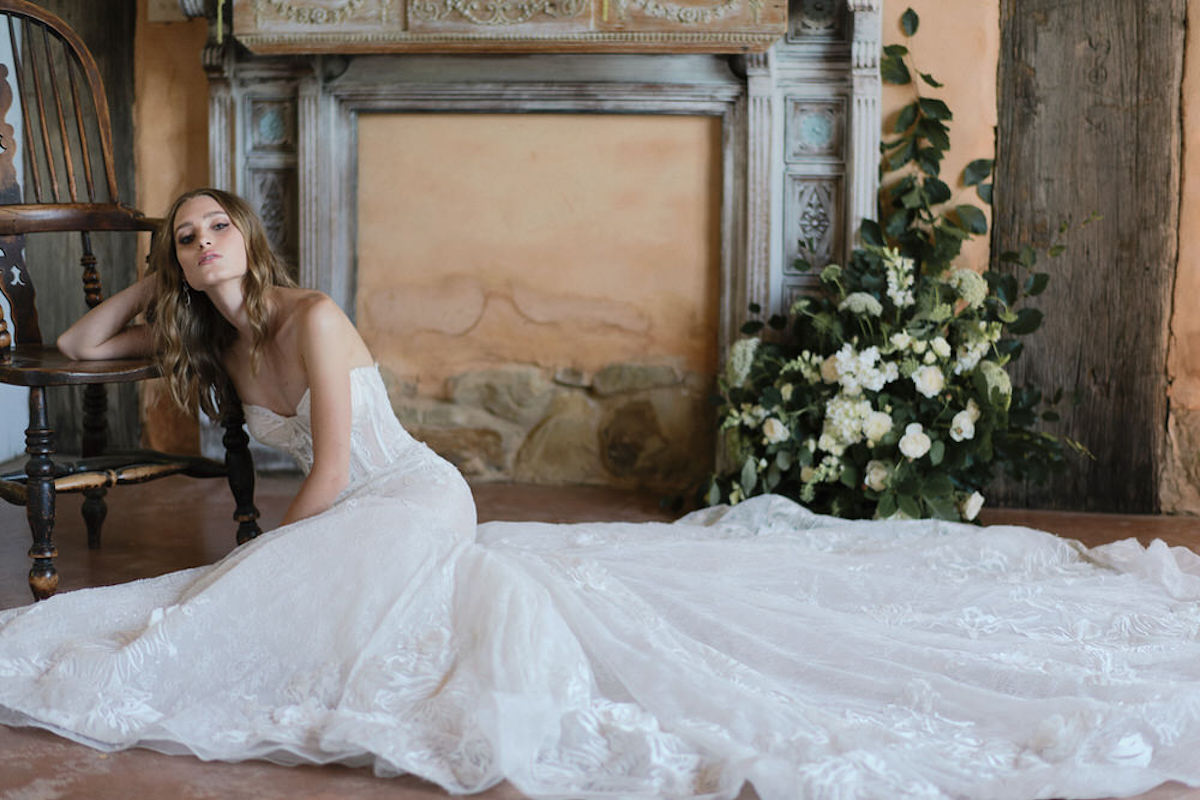 french_bride_leaning_on_chair_inside_rustic_building.jpg