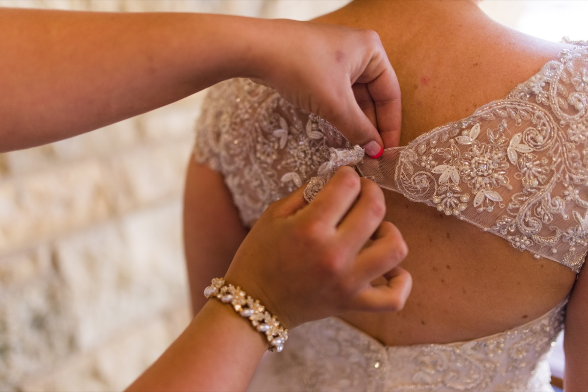 getting_ready_bridesmaid_buttoning_back_of_brides_dress.jpg