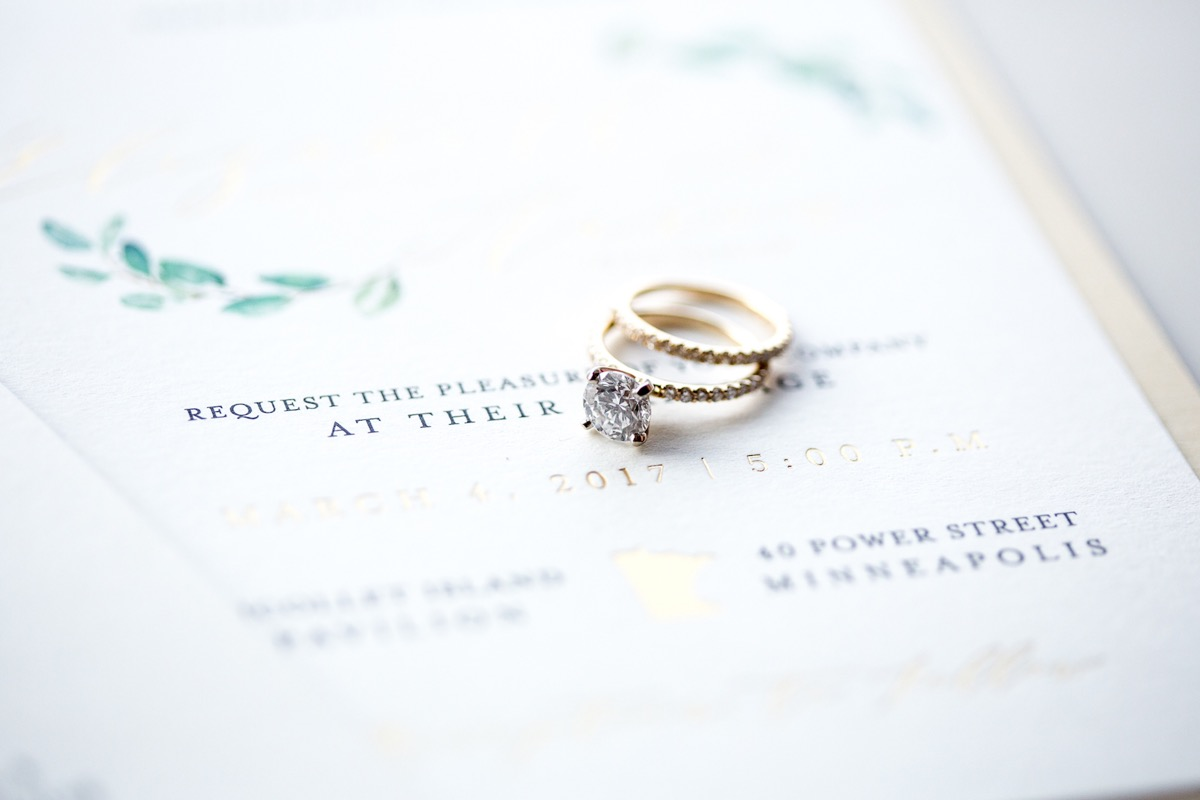 gold_bands_silver_diamond_stacked_on_wedding_invitation.jpg