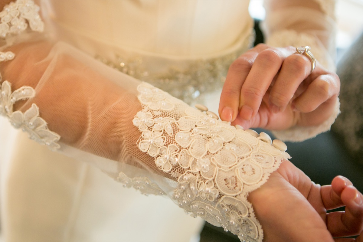 gold_ring_white_diamond_bride_buttoning_white_buttons_on_lace_sleeve_wedding_dress.jpg