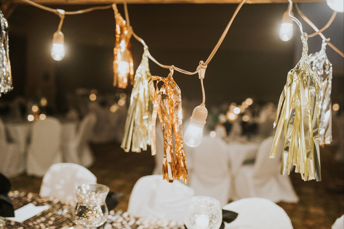 gold_wedding_streamers_and_tea_lights_hanging_over_reception_tables.jpg