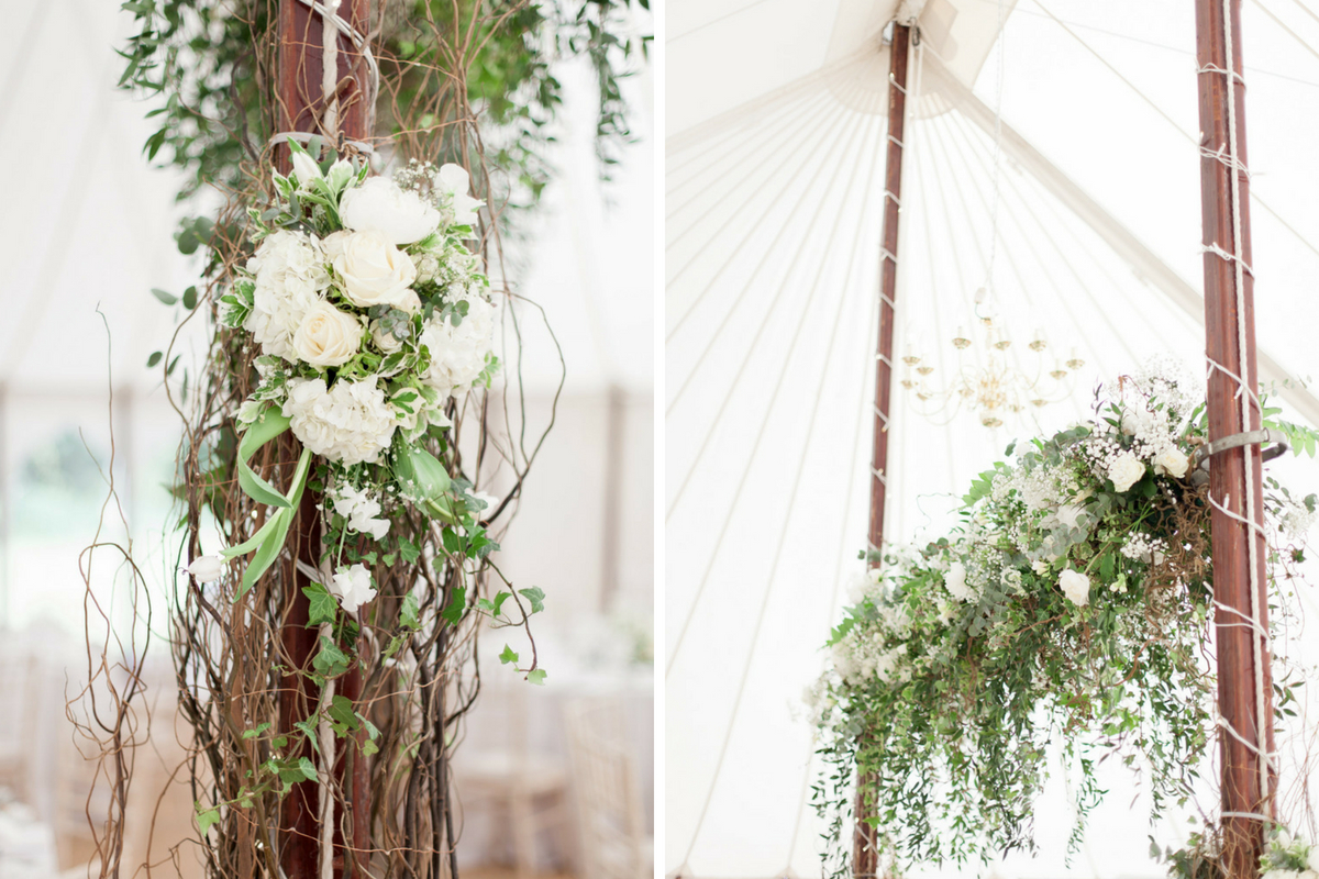 green_and_brown_florals_hanging_from_white_tent_wedding_reception.jpg