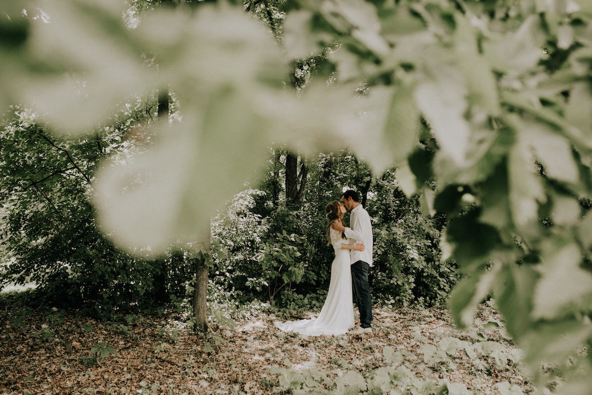 green_leaves_framing_bride_and_groom_kissing.jpg