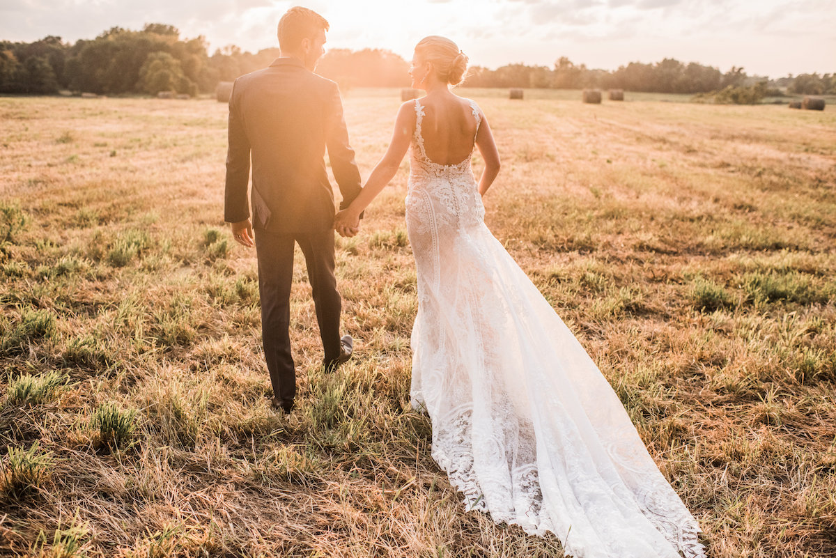 groom_and_bride_with_long_train_holding_hands_at_sunset.jpg