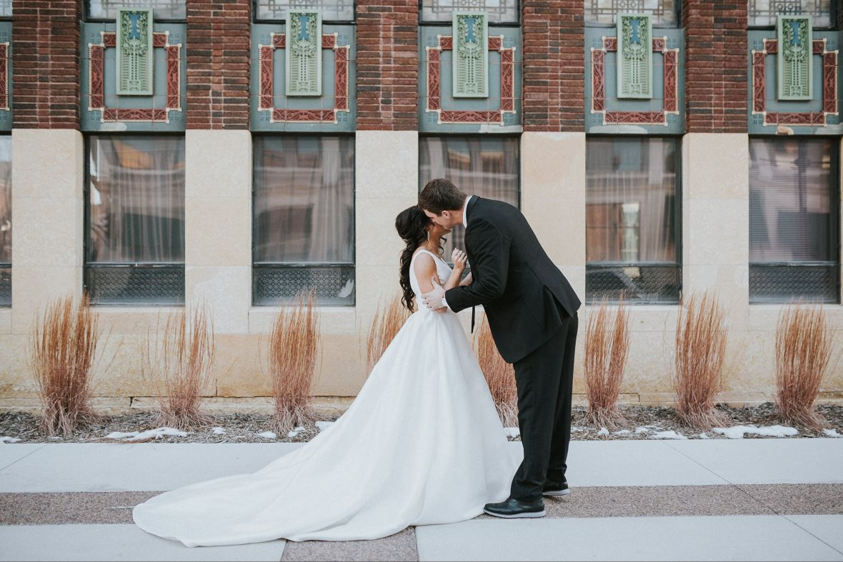 groom_bending_down_to_kiss_brides_cheek_outside_winter.jpg