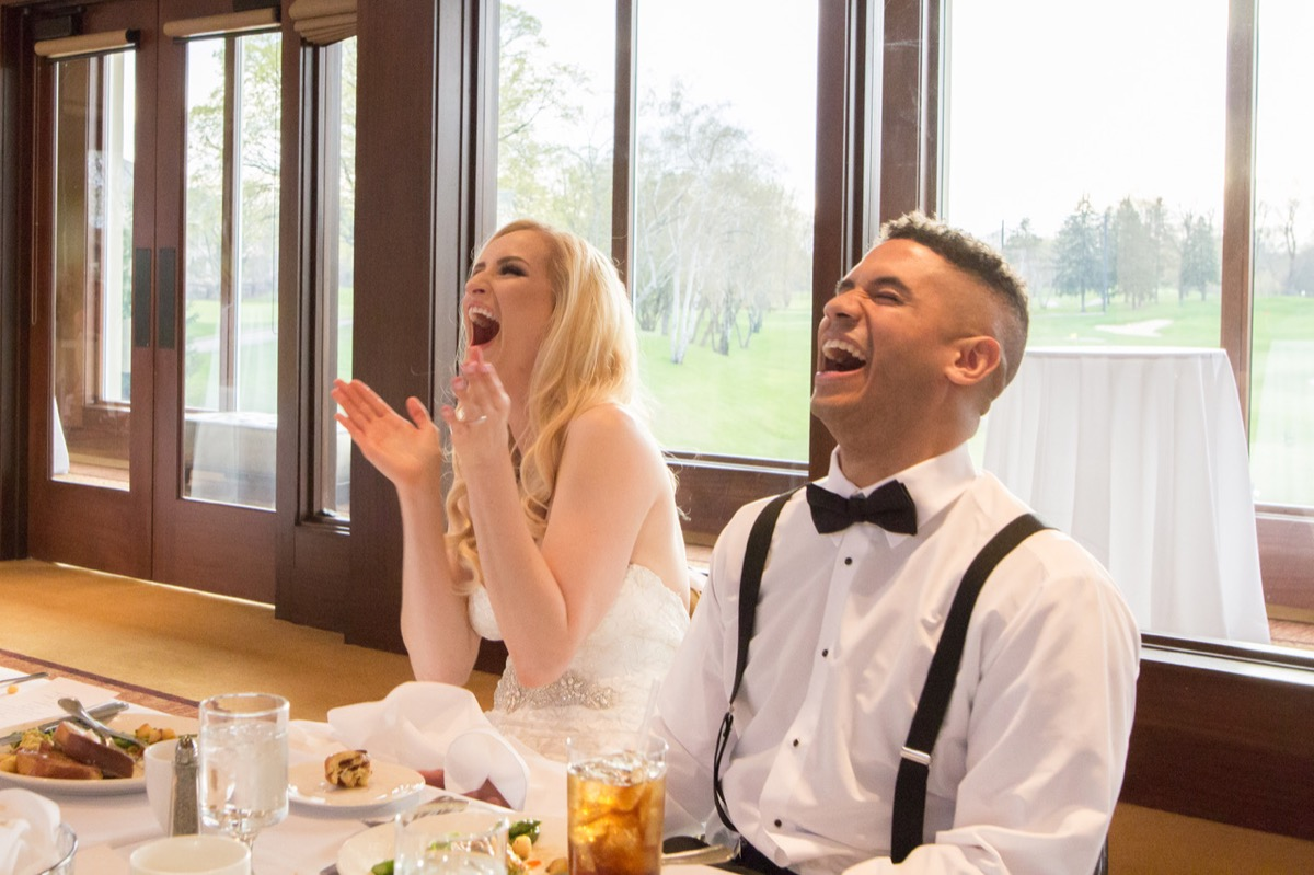 groom_black_suspenders_bride_laughing_clapping_hands.jpg