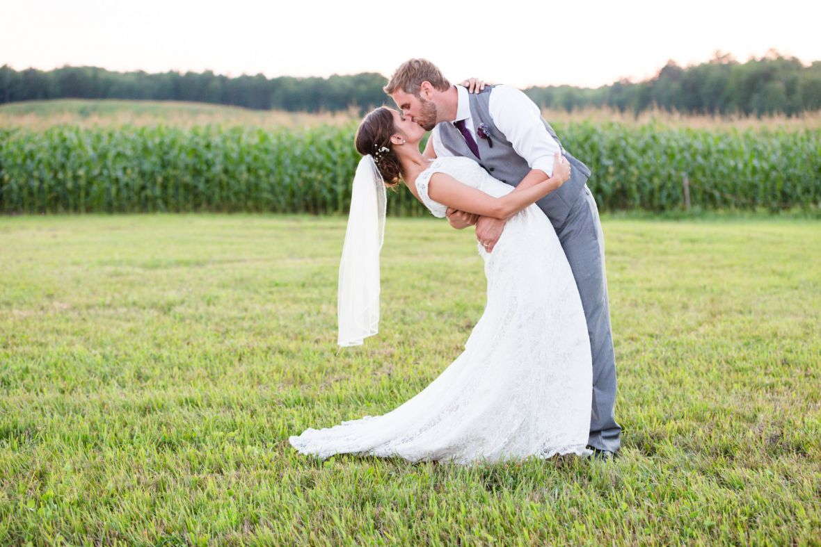 groom_dipping_bride_for_a_kiss_corn_stacks_behind.jpg