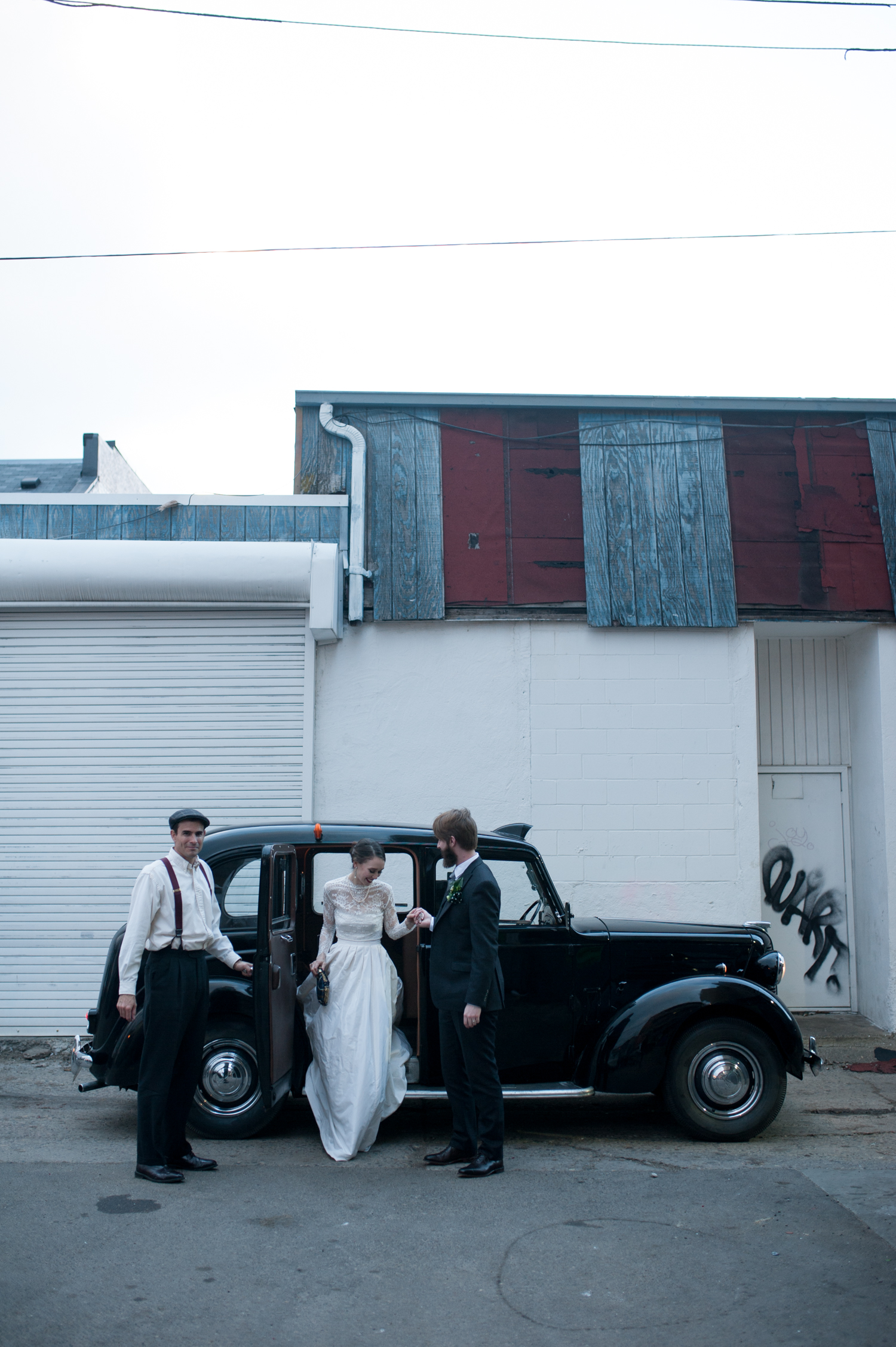 groom_helping_bride_exit_vintage_car_rental_transportation_from_ceremony_to_reception.jpeg