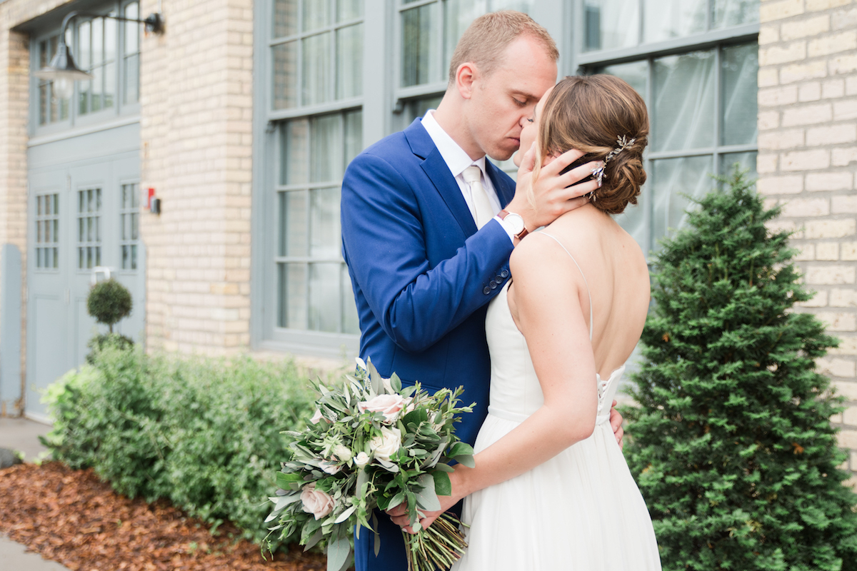 groom_holding_brides_face_kissing_eyes_closed_in_front_of_brick_building.jpg