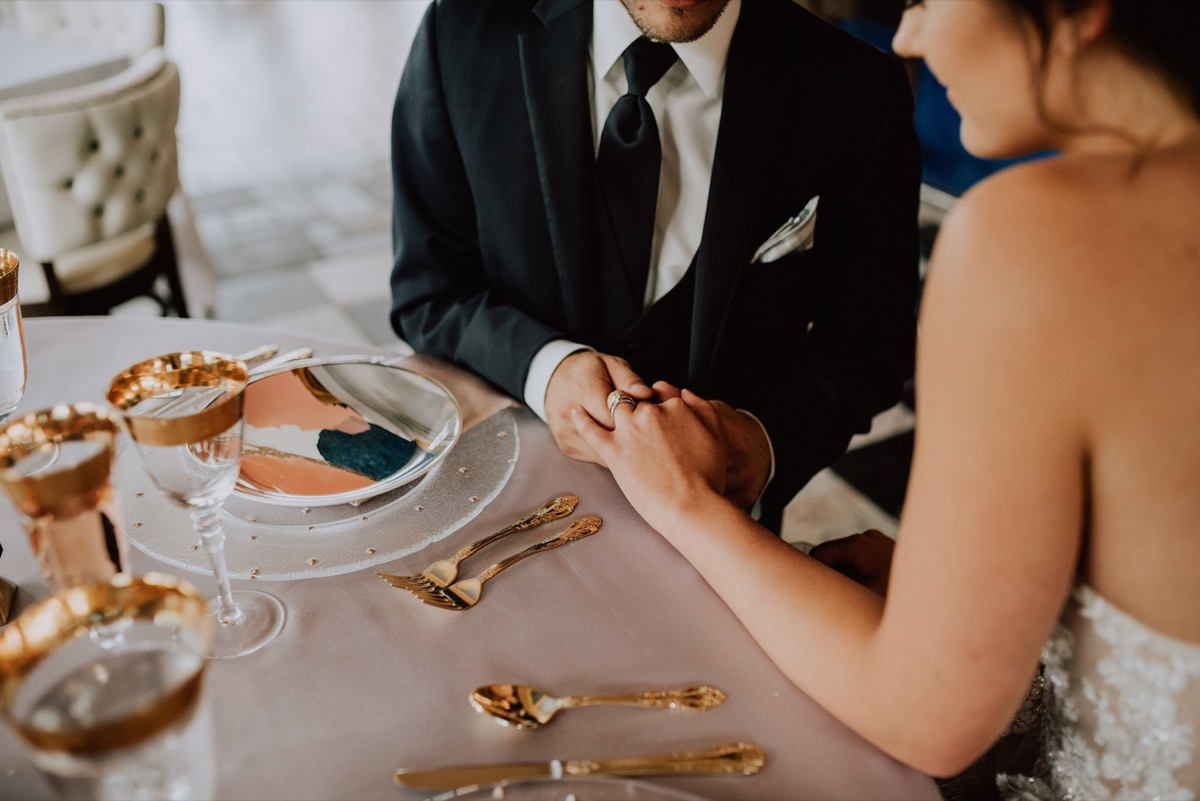 groom_holding_brides_hand_table_reception_table.jpg