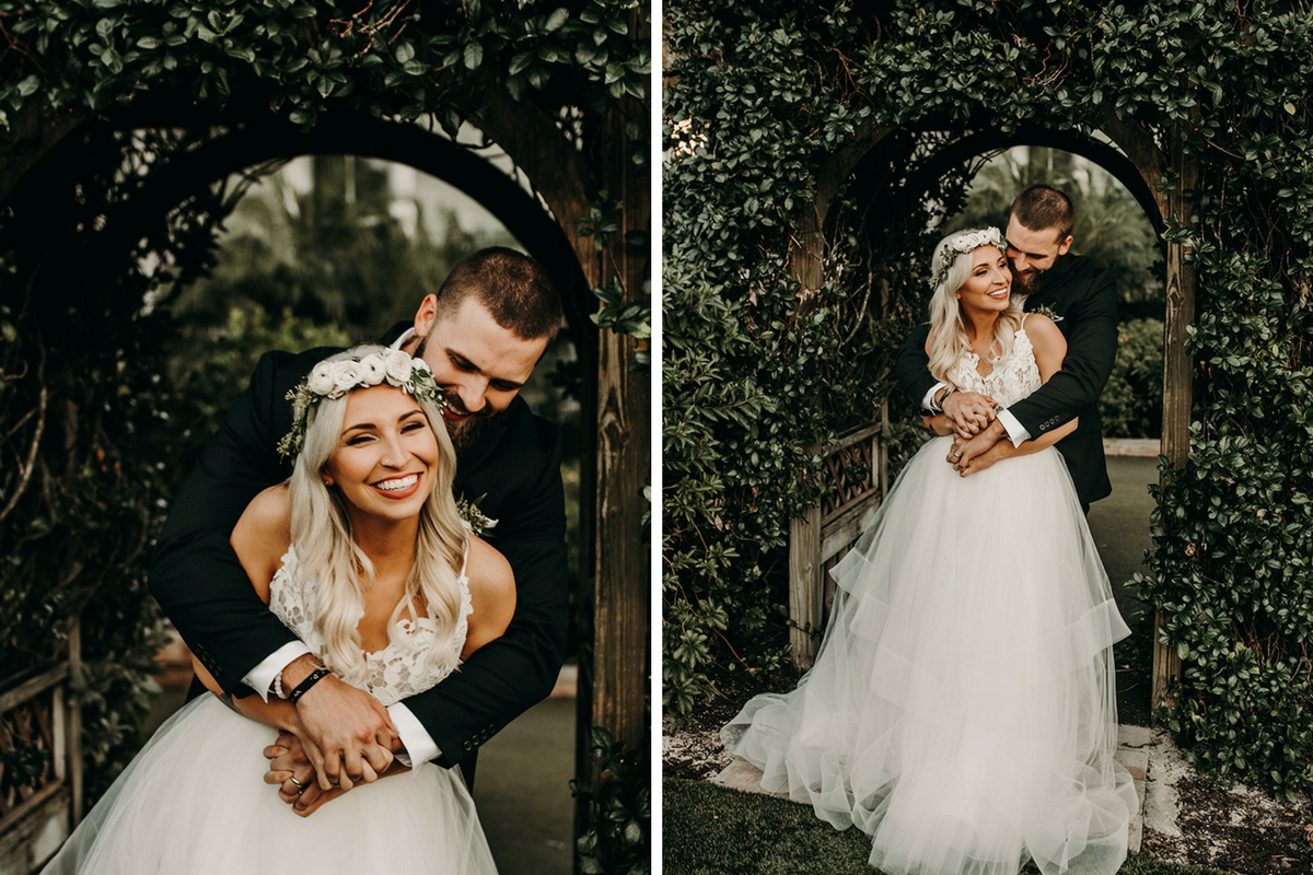 groom_hugging_bohemian_bride_laughing_garden_arch.jpg