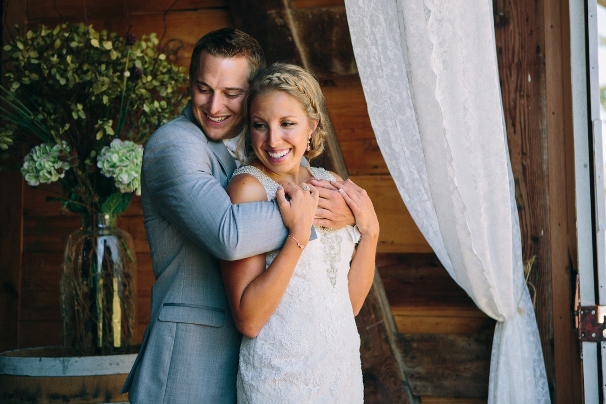 groom_hugging_bride_from_behind_white_lace_curtains.jpg