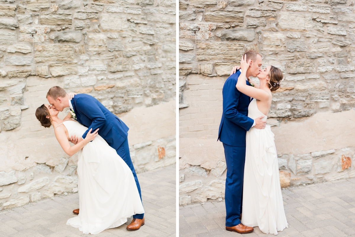 groom_in_navy_suit_dancing_with_bride_kissing_her_holding_waist_with_stone_wall_backround.jpg