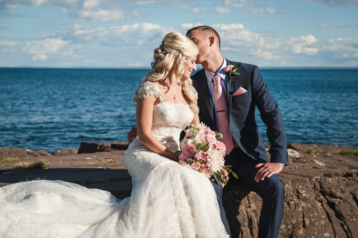 groom_kissing_bride_sitting_on_lakeside_rocks.jpg
