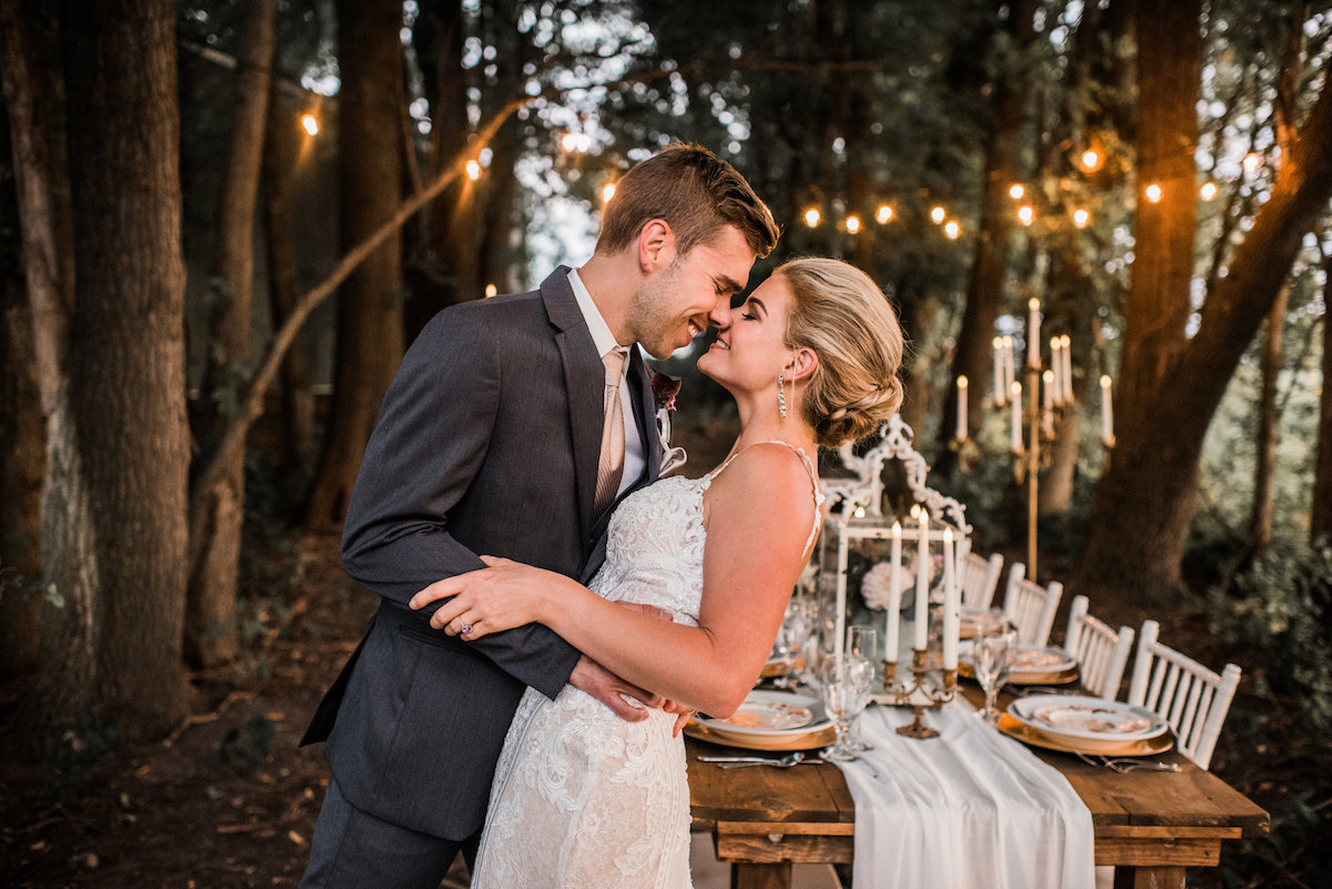 groom_kissing_bride_smiling_twinkling_lights_wooded_wedding_dinner.jpg