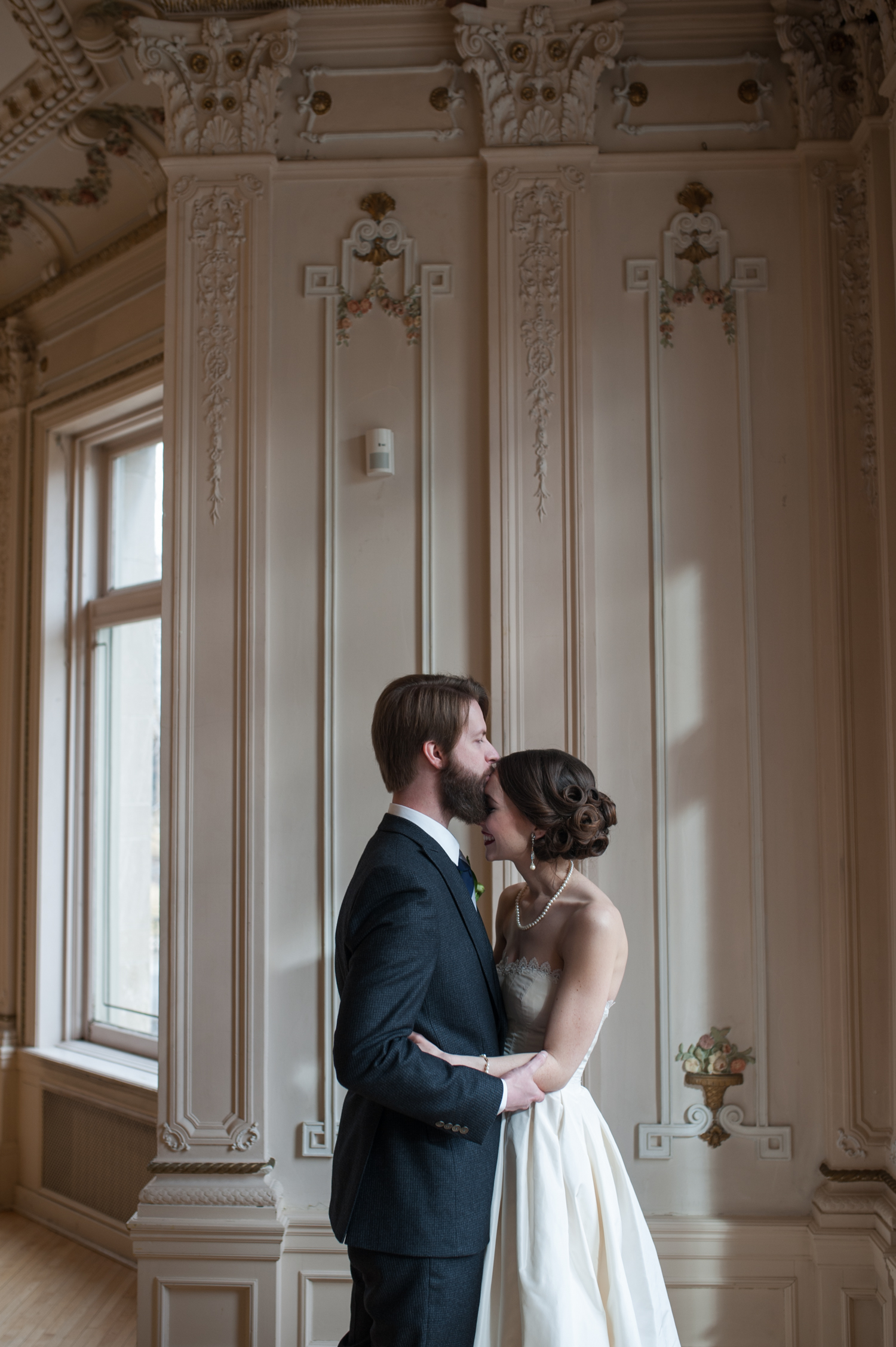 groom_kissing_brides_forehead_as_she_smiles_inside_classy_wedding_venue.jpeg