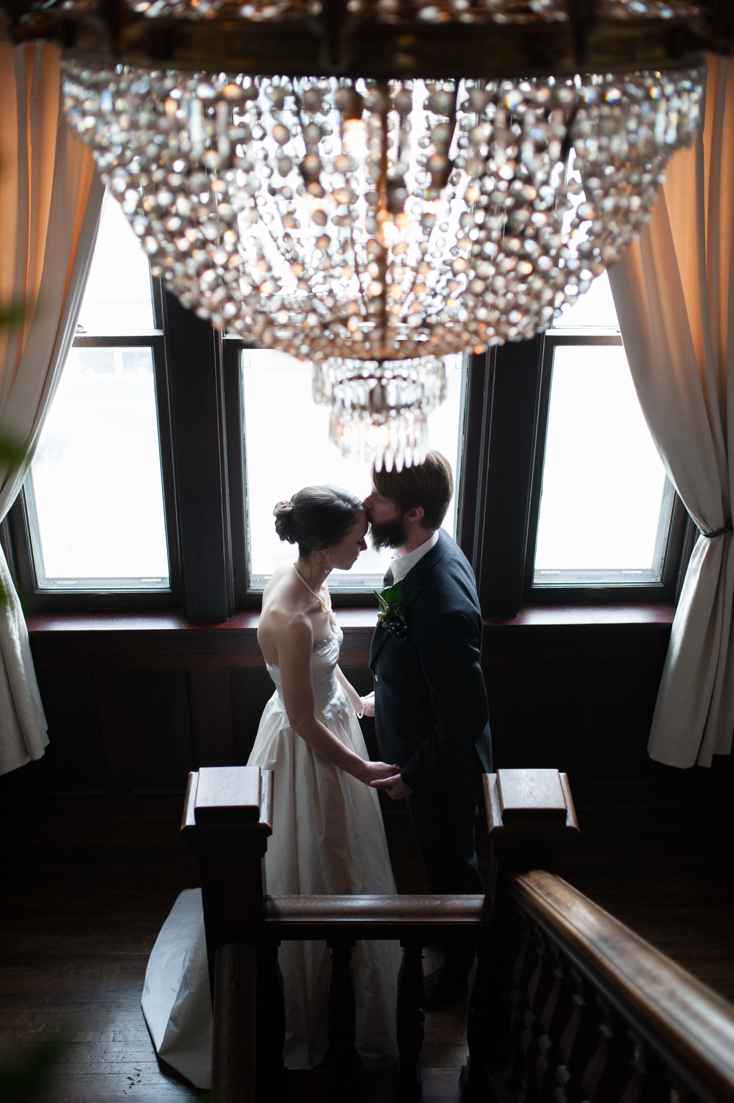 groom_kissing_brides_forehead_inside_fancy_minneapolis_wedding_venue_with_chandelier_and_windows.jpeg