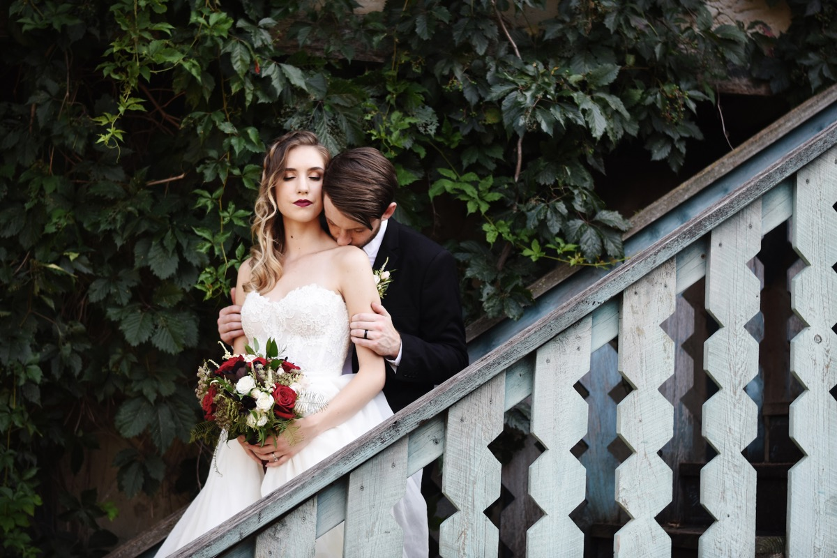 groom_kissing_brides_shoulder_staircase_greenery.jpg