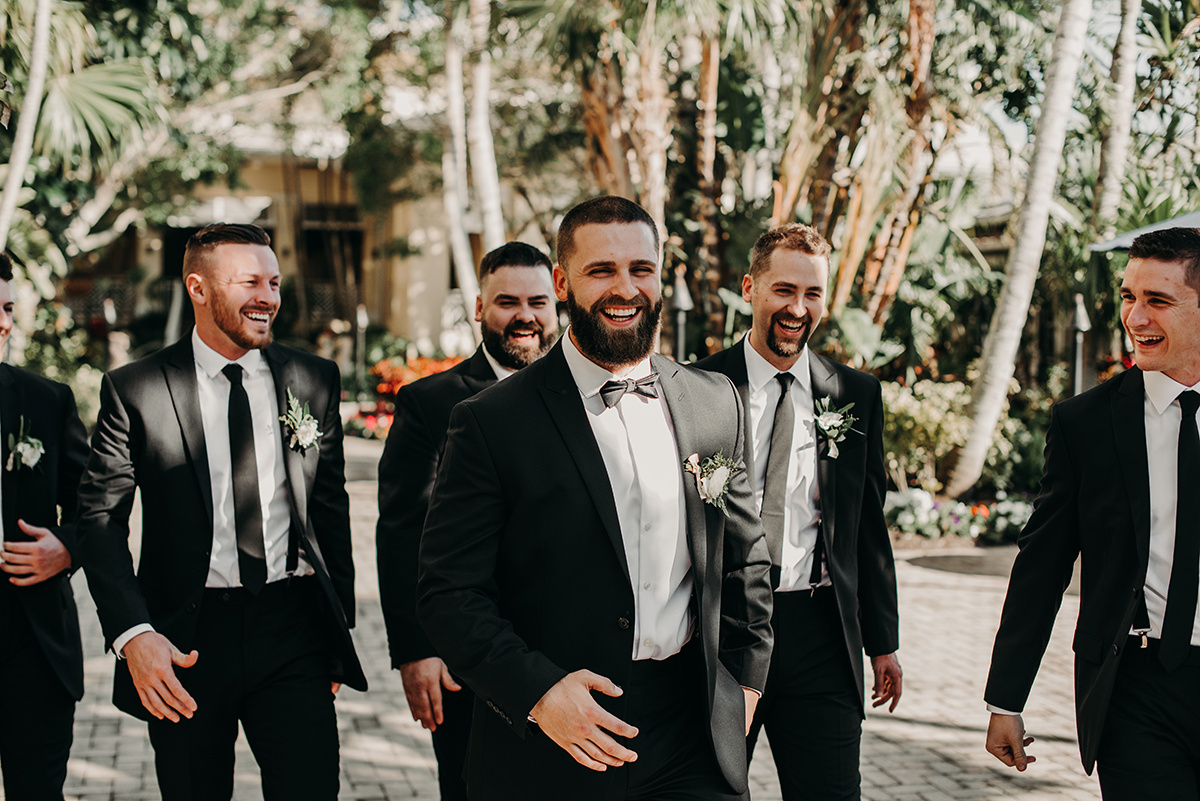 groom_laughing_walking_with_groomsmen_outside_sunny_florida.jpg