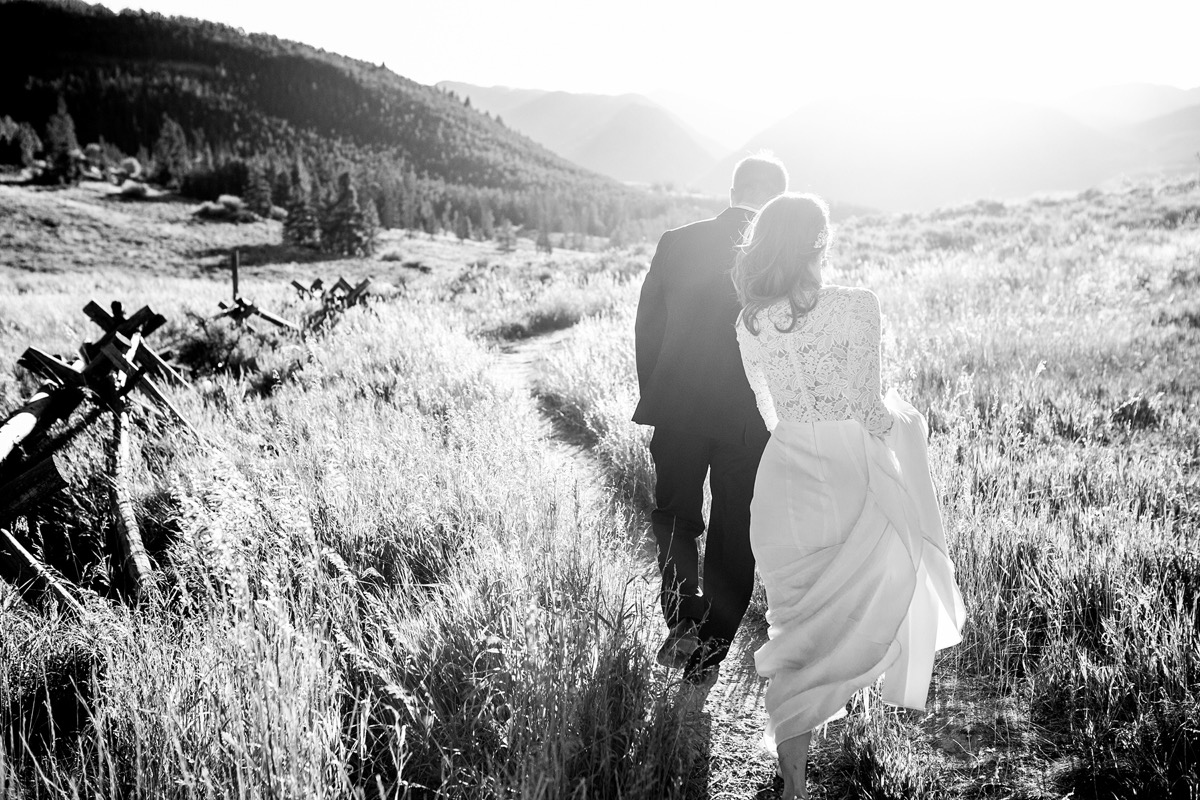 groom_leading_bride_away_into_field_black_and_white_photo.jpg