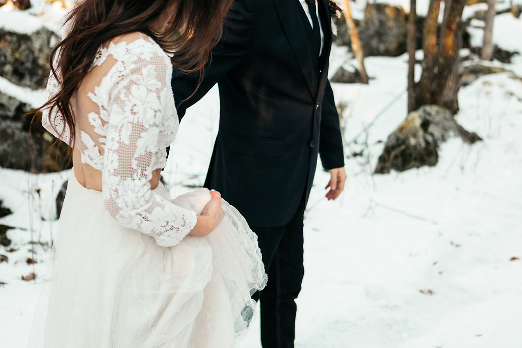 groom_leading_bride_through_the_snow_holding_hands.jpg
