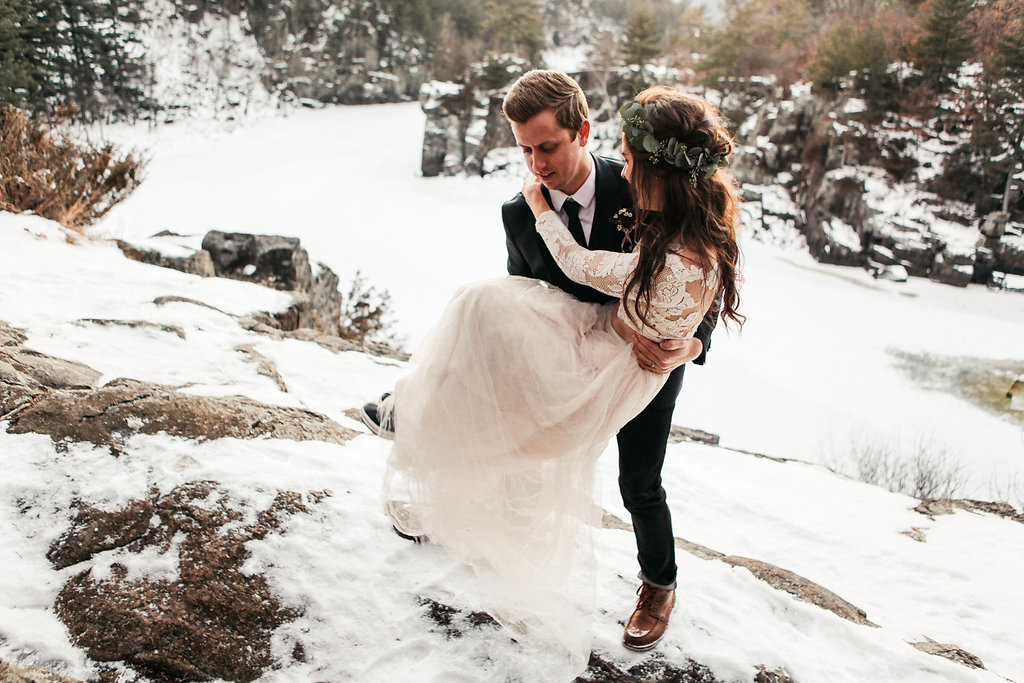 groom_picking_up_holding_bride_in_the_snow_.jpg