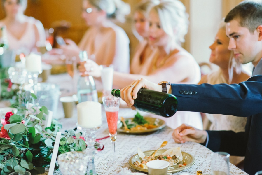 groom_pouring_champagne_into_glass_wedding_reception.jpg