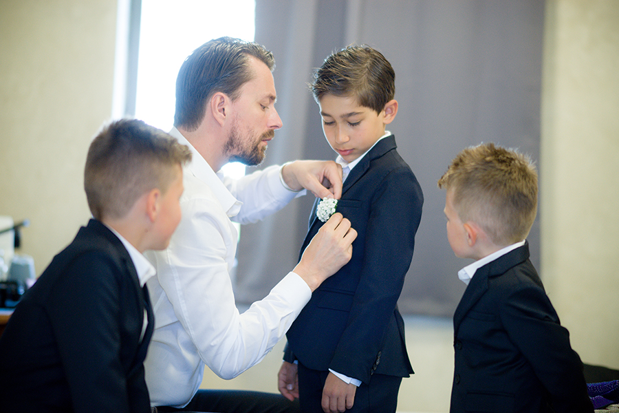 groom_putting_boutinerre_on_son_in_navy_tux.jpg
