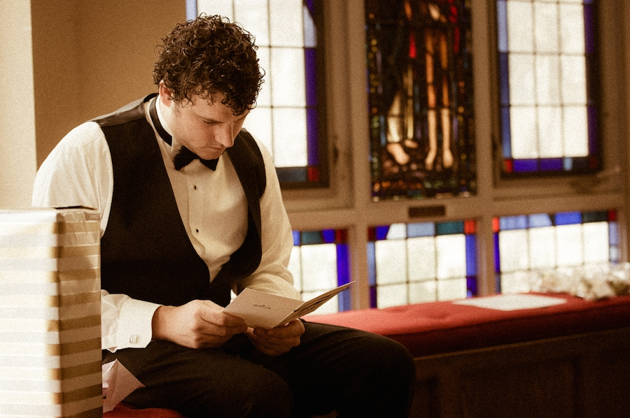 groom_sitting_on_red_cushions_reading_brides_letter.jpg