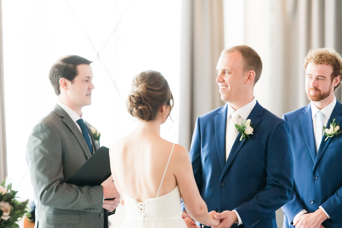 groom_smiling_at_officient_during_ceremony_navy_tux_holding_brides_hands.jpg