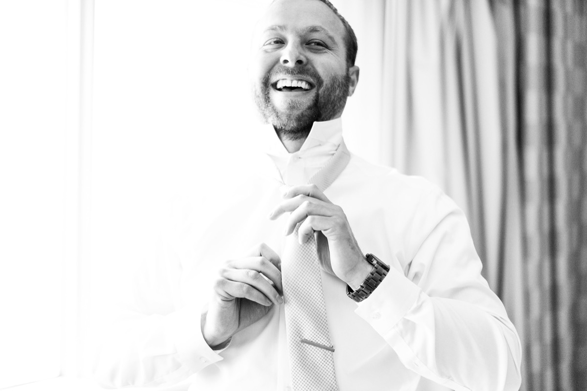 groom_smiling_getting_ready_black_and_white_picture.jpg