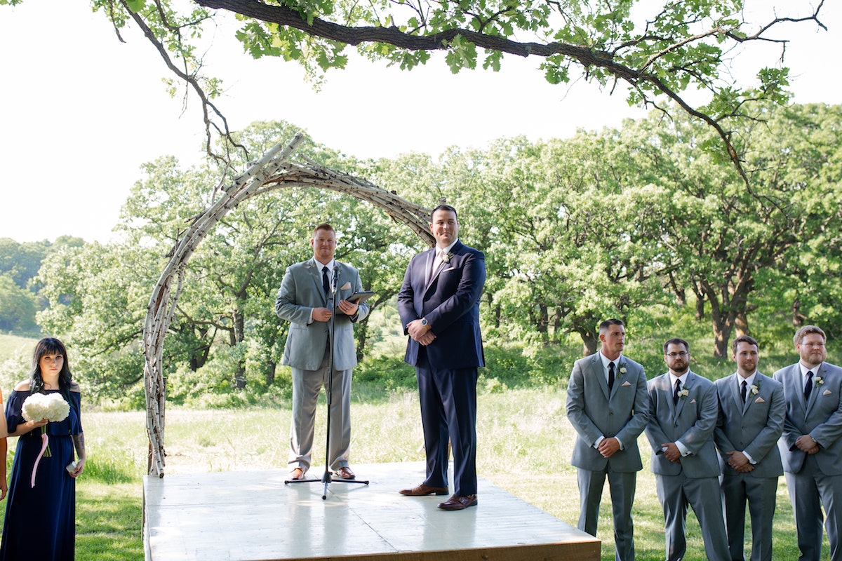 groom_standing_on_raised_platform_outdoors_watching_bride_wooden_arch.jpg