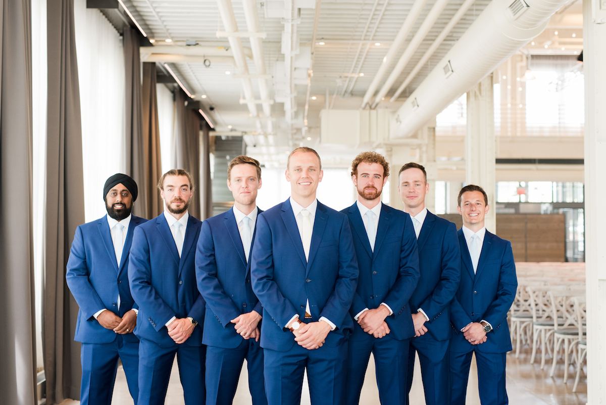 groom_standing_with_groomsmen_in_industrial_wedding_venue_all_navy_suits_hands_crossed.jpg