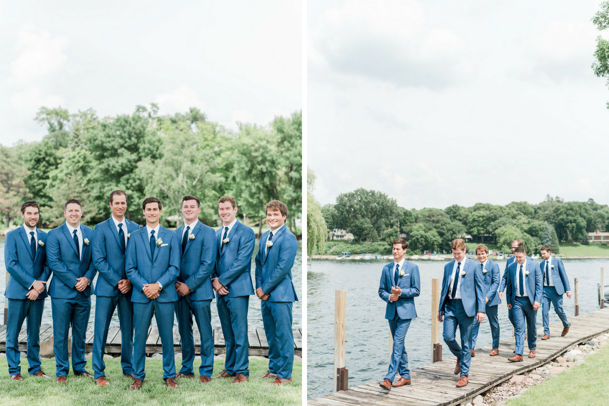 groom_walking_with_groomsmen_navy_suits_lakeside_dock_green_trees.jpg
