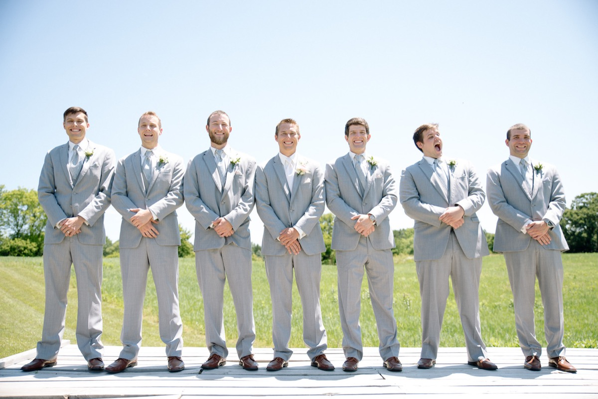 groomsmen_hands_folded_in_front_light_gray_tuxes_brown_shoes.jpg