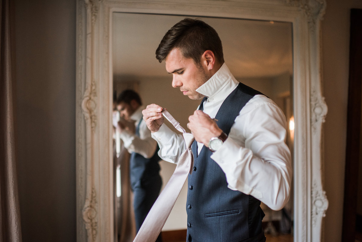 handsom_groom_preparing_for_wedding_large_mirror.jpg