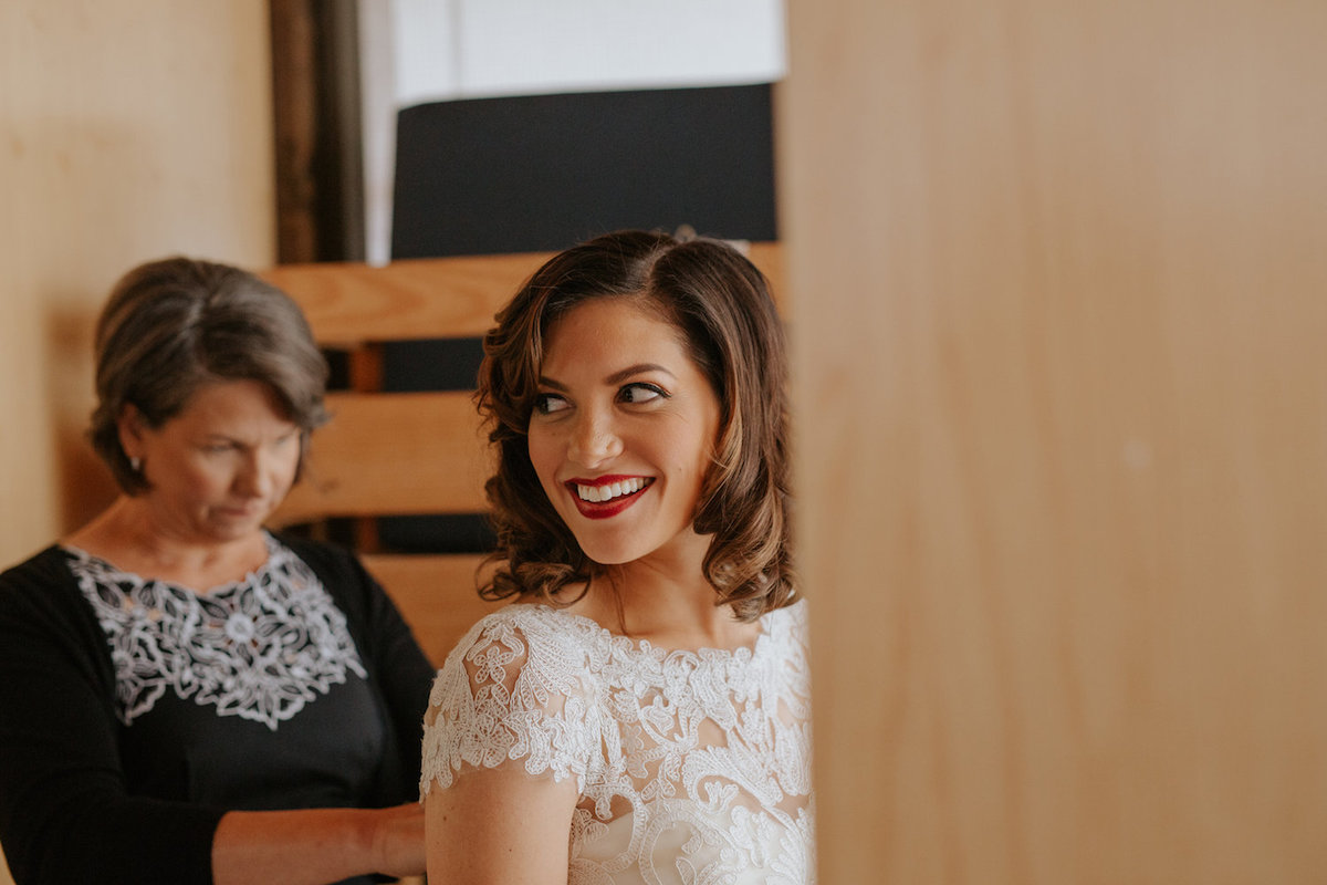 happpy_bride_getting_wedding_dress_buttoned_by_mom.jpg
