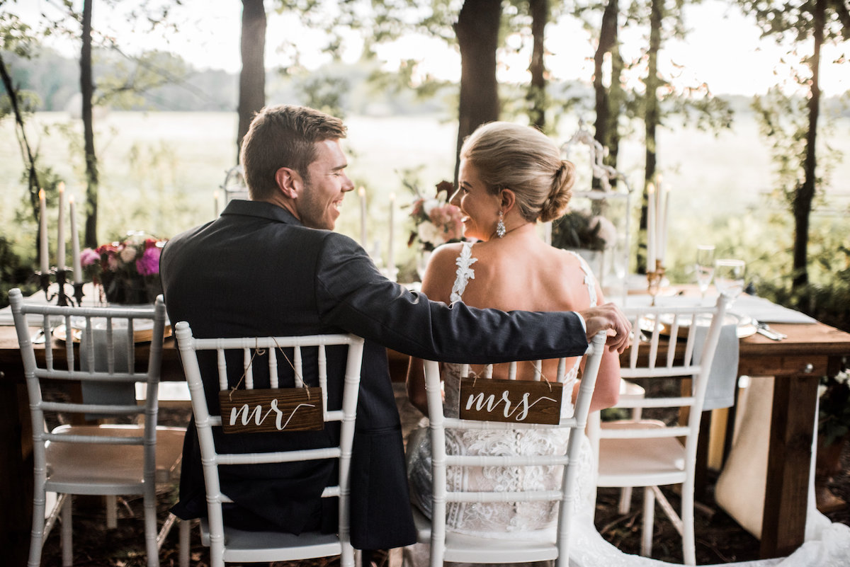 happy_bride_and_groom_laughing_sitting_in_wedding_chairs.jpg